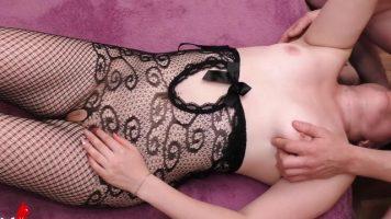 امرأة شابة ذات ثديين صغيرين جدًا تمارس الجنس في الفم عند حافة السرير