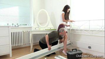 رجل ناضج يساعد امرأة شابة في ترتيب الغرفة ويتحمس عندما يراها
