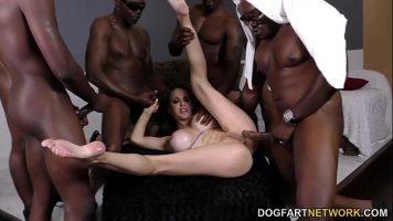 امرأة سمراء ذات ثديين كبيرين للغاية ومحاطة بالعديد من السود الذين يقدمونها لها