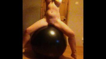 الفتاة التي تحب عمل جسدها في صالة الألعاب الرياضية تقفز على كرة عارية